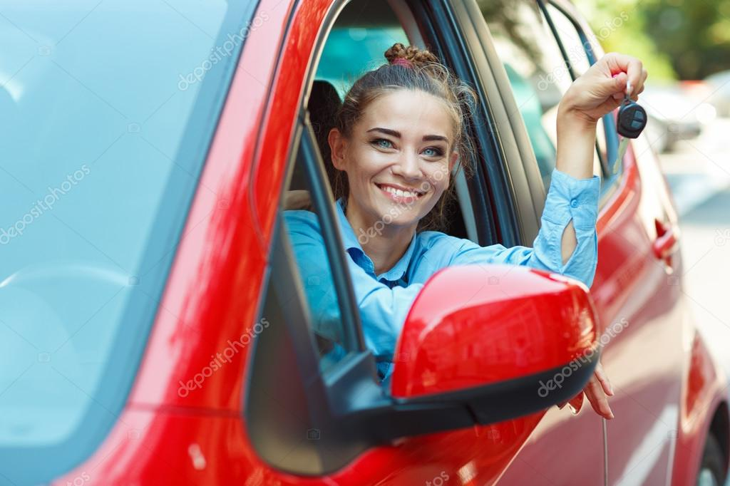 Young cheerful woman sitting in a car with keys in hand - concep