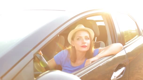 Smiling woman driving a car at sunset