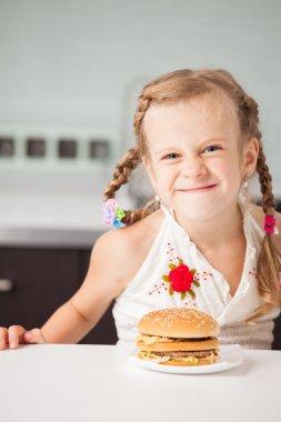Child with hamburger at kitchen stock vector
