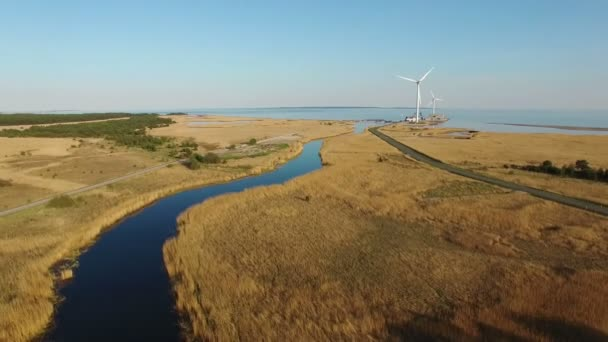4k high flight over blue river and fields towards wind turbines and