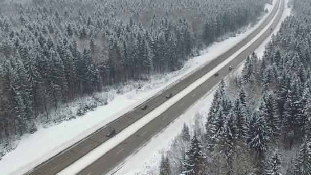 Silnice v zimním lese s řízením auta. Letecký panoramatický pohled. Úběžník perspektivy.