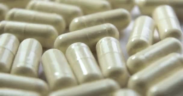 Viele beige Pillen rotieren auf weißem Hintergrund, Nahaufnahme.
