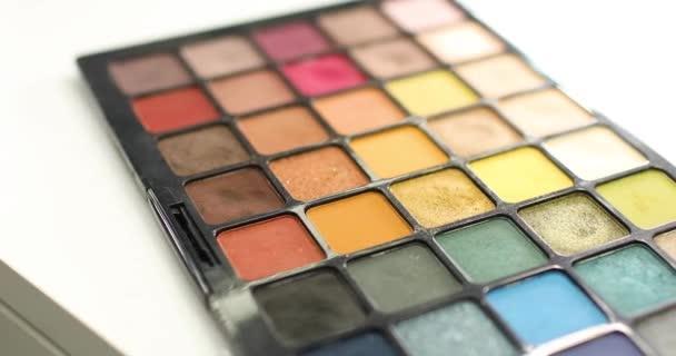Make-up umělec bere oční stíny z profesionální kosmetické palety pomocí štětce.