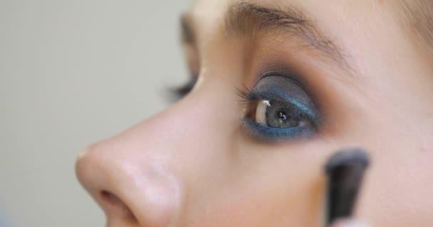 Make-up umělec je korekce make-up pod očima na ženské tváře, boční pohled.