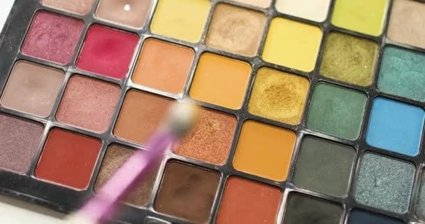 Visagiste takes eyeshadows from professional cosmetics palette using brush.