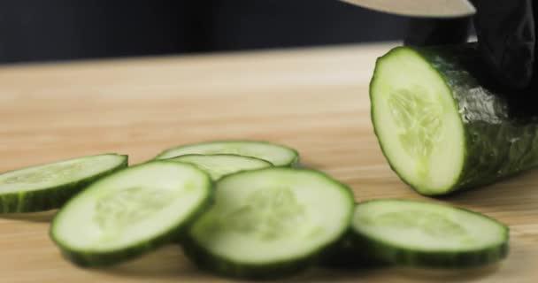 Szakács kesztyű vágás az uborka szeletek, közelkép.