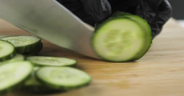 Szoros kilátás szakácsok kezét fekete kesztyűben vágás friss uborka szeletek.