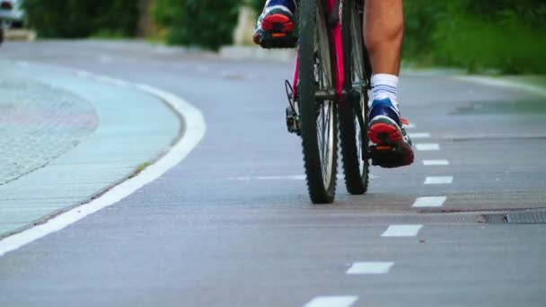 Cyklisté jezdí na červenou cyklostezce vedle pěší chodník.