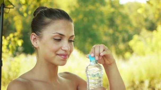 portrét mladé krásné ženy s odhalenými rameny pije z láhve studené vody, na zeleném pozadí letní přírody