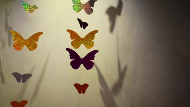 Butterflies, which cut the foil hang on a thread on wall background.