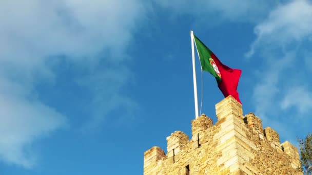 Portuguese flag on Sao Jorge Castle is a Moorish castle occupying a commanding hilltop overlooking the historic centre of the Portuguese city of Lisbon and Tagus River.