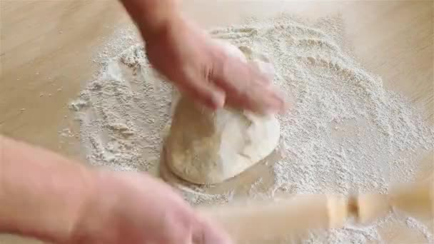 Woman with a rolling pin rolls yeast dough made of wheat flour on a wooden table.