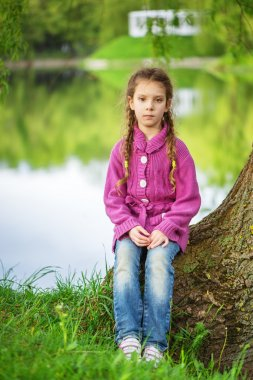 Little girl sits near lake