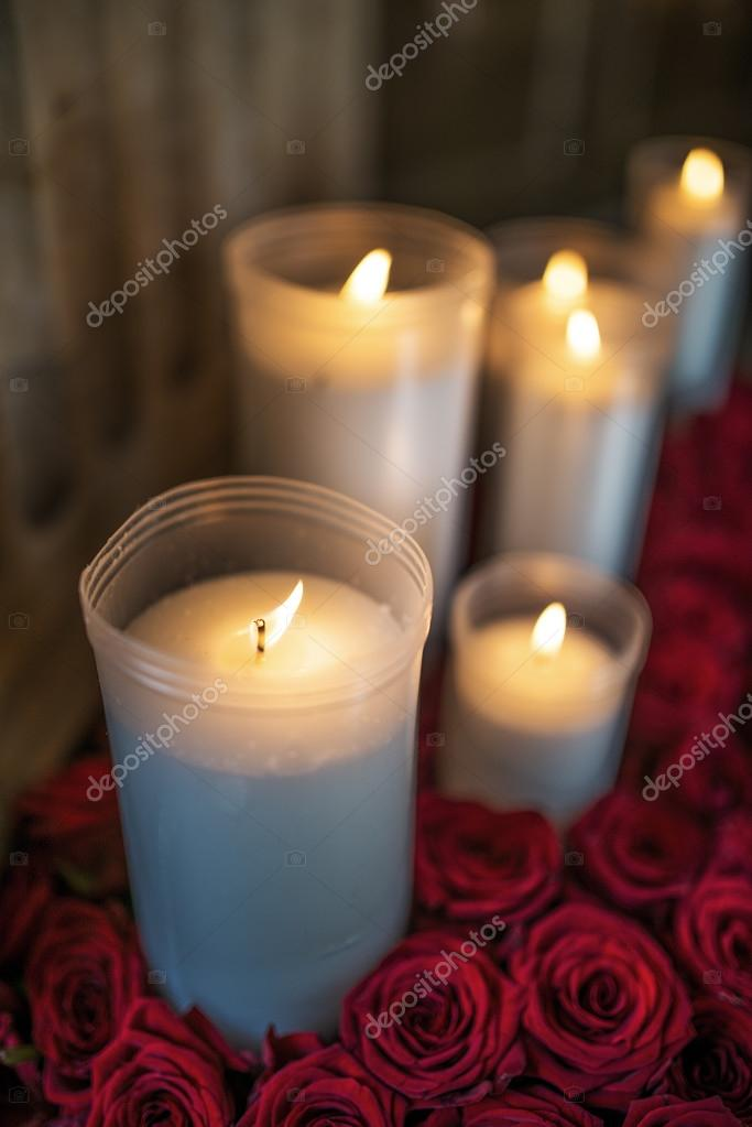 Burning candles in plastic cups surrounded