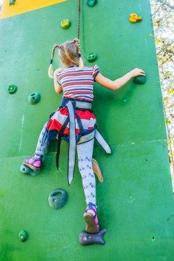 Little girl talking trains on climbing wall