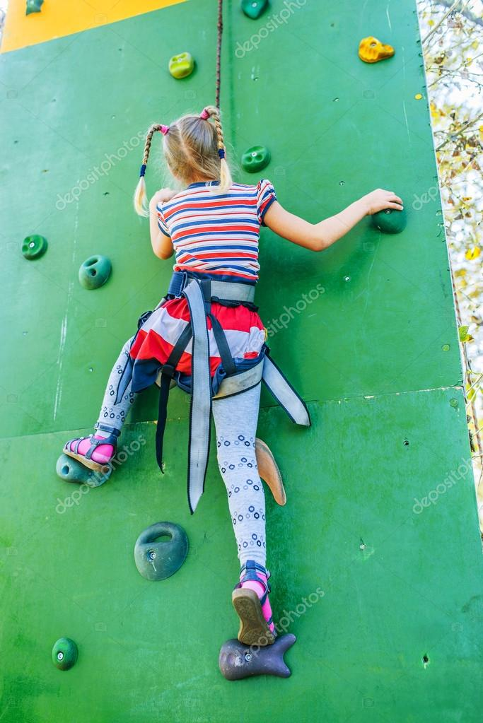 Little girl talking trains on climbing wall
