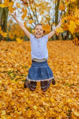 Little girl jumping on background of yellow leaves