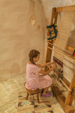 Girl sits at old loom