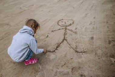 Little girl sand draws funny man