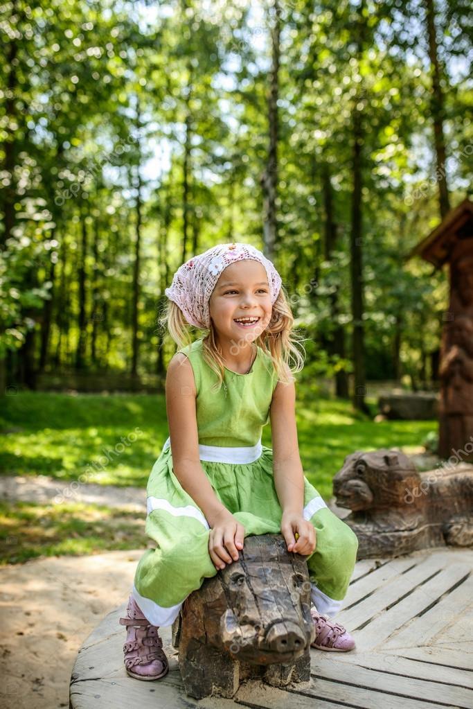 Smiling little girl swinging on wooden pig