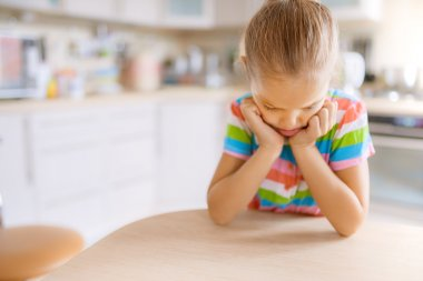 little girl sitting at the table and sad
