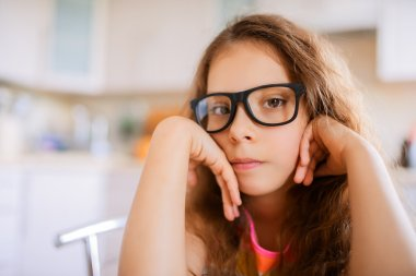 Little pretty thoughtful girl in glasses
