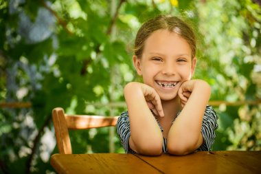 Little beautiful girl of wooden table