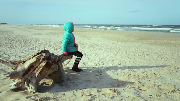 kleines schönes trauriges Mädchen sitzt am Meer