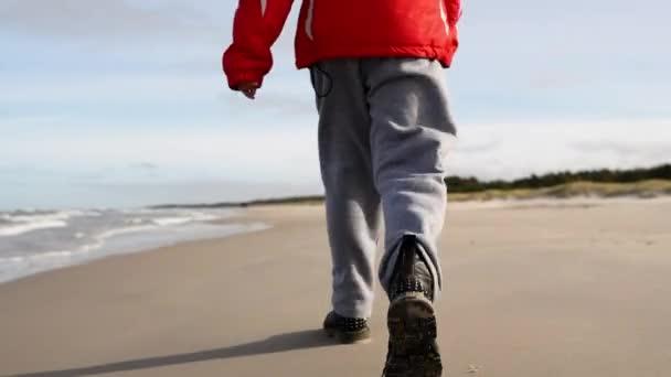 Malá holčička chodí podél pobřeží Baltského moře