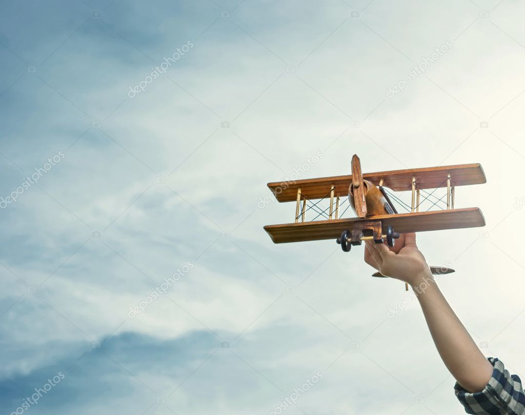 Hand with wooden airplane