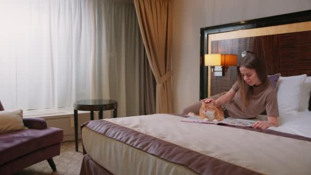 Mladá dívka čtení s kočkou v pokoji