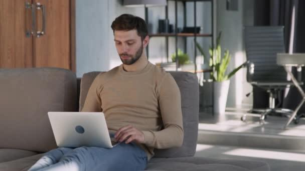 Müder junger Mann tippt zu Hause auf Laptop im Zimmer.