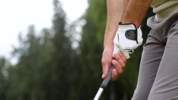 Ruce hravého muže držícího golfovou hůl