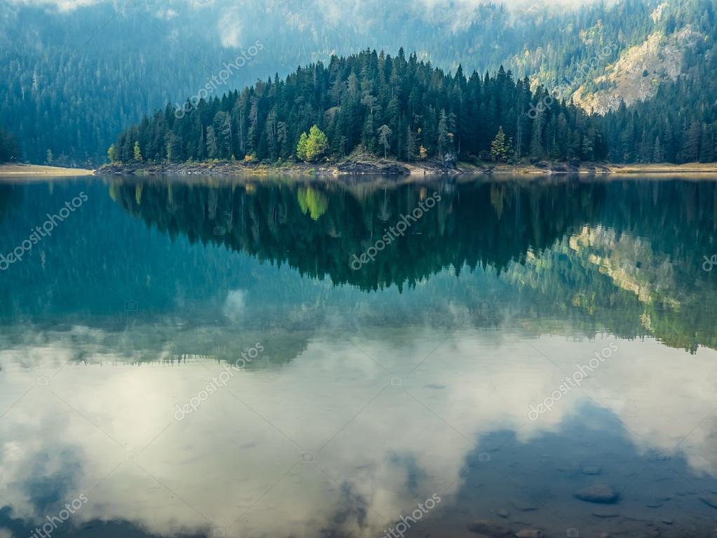 Deep blue lake near the mountains stock vector