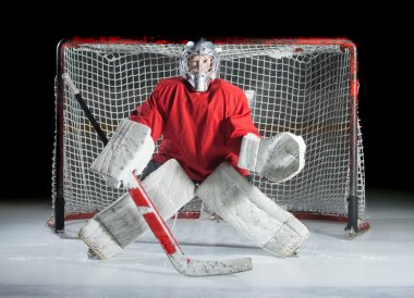 A young ice-hockey goaltender in a ready position against a dark