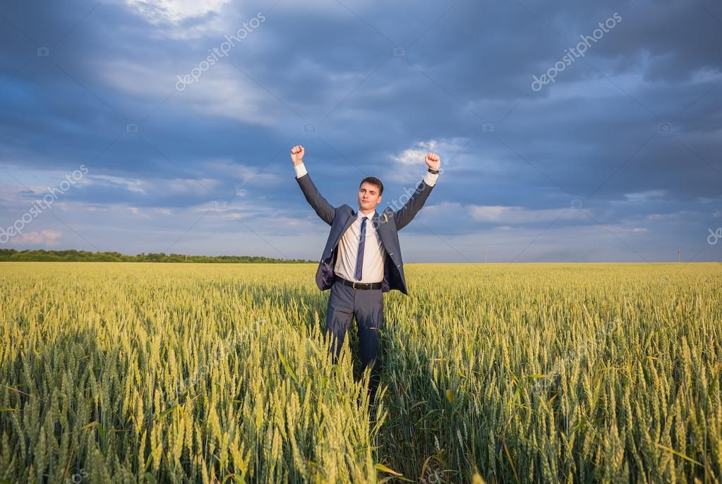 happy farmer, businessman, standing in wheat field with his hands and thumbs up