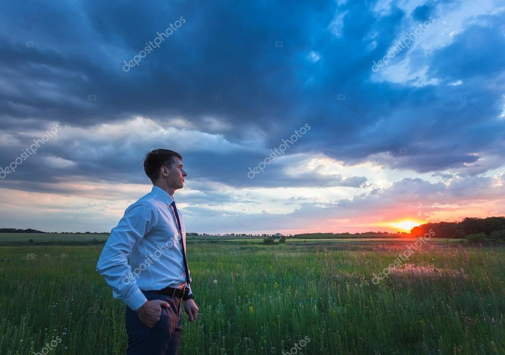 happy farmer, businessman, standing in field with his hands and thumbs up