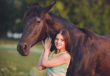 Young beautiful girl with frisian horse standing in the meadow