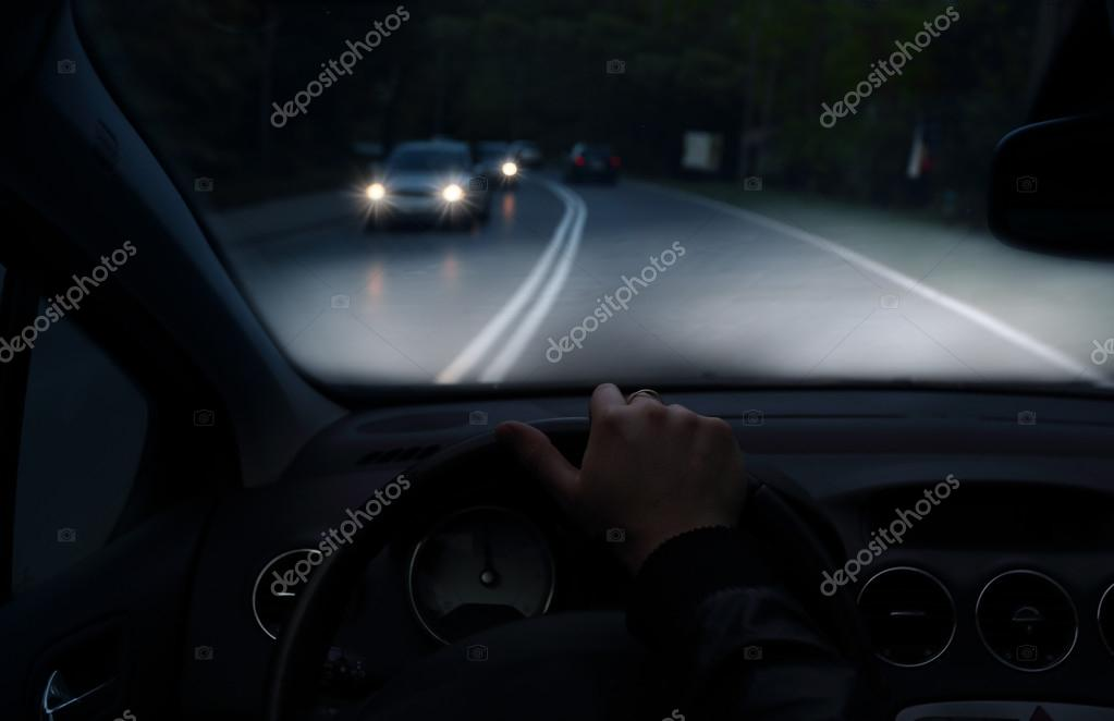 rijden met een auto met xenon verlichting s nachts stockfoto