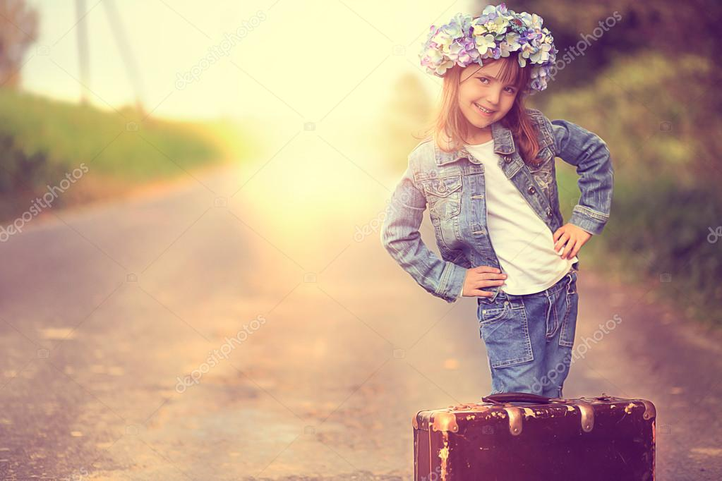 Pretty girl in a wreath and a denim jacket with an old suitcase