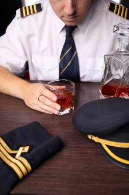 The pilot in uniform drinking alcohol