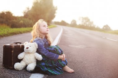 Orphan sits alone on the road with a suitcase