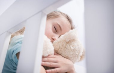 Sad young girl hugging a teddy bear in a child's room