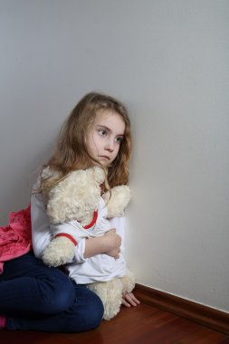 Introverted child sitting with teddy bear