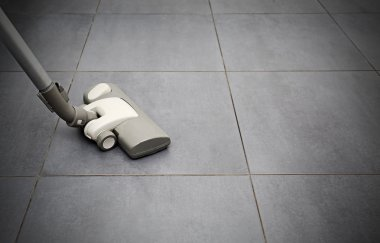 Vacuuming flooring in kitchen