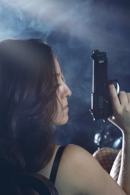 Enigmatic and mysterious woman with gun