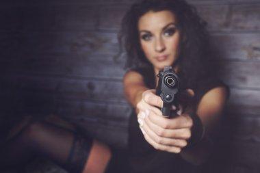 A pretty girl holding a gun