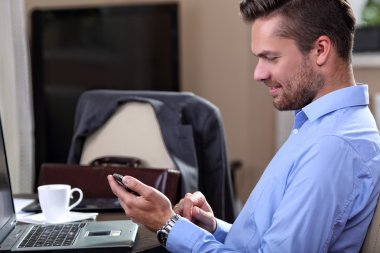 Young businessman checks the messages on the phone at home