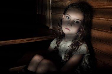 Depressed girl sitting in a dark hallway in home