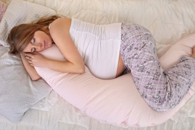 Pregnant woman sleeping peacefully in the bedroom